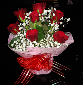 12 luxury stunning red roses, with greenery and pretty white gypsophilia in a vase beautifully wrapped with a bowtie.
